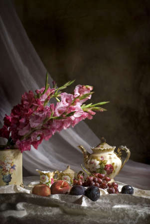 Vertical image of fruit and gladiola flowers with old fashioned tea set  Stock Photo