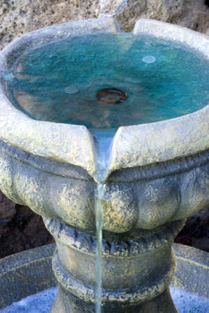 Vertical close up shot of coins in a small fountain water feature