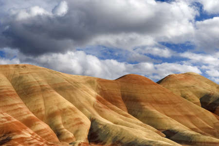 Horizontal landscape of the colorful Painted Hills in Oregon aganist cloudy blue skies