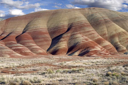 rock layers: Horizontal landscape of the colorful Painted Hills in Oregon aganist cloudy blue skies