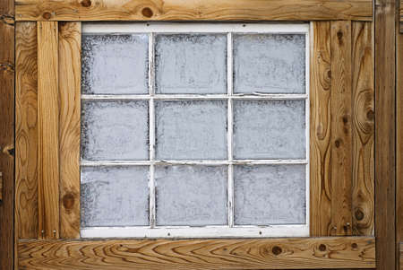 Horizontal image of an old wooden nine-lite window pane in a wooden wall, covered in ice crystals