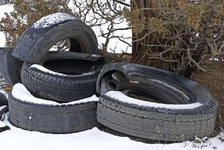 A pile of destroyed tires dumped on public lands, littering the landscape