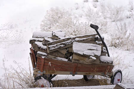 Wooden-sided red wagon loaded with firewood sits stranded in the snow after a snowstorm  Stok Fotoğraf