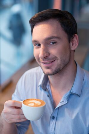 revel: Revel in best taste. Portrait of handsome delighted man holding cup of coffee and  drinking it while smiling Stock Photo