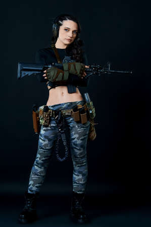 Dressed in a black T-shirt, a curvy combat woman with short hair holds a rifle against a dark background.