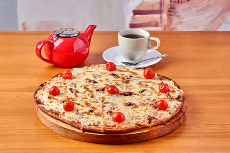 pizza Lombardy lies on a stand with tea and a kettle