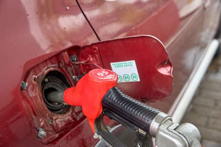 the gun is inserted into the gas tank of the car Reklamní fotografie