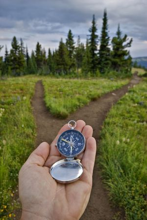 compass: A compass is held out at a junction in the trail to check for direction. Stock Photo