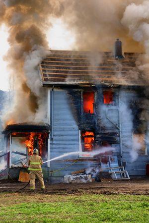 house on fire: Un �nico bombero dispara su towarda de manguera una casa ardiendo Foto de archivo