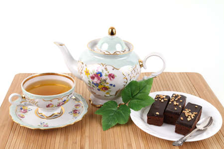 caffeine free: Teapot and cup of tea with 3 brownies on white background Stock Photo