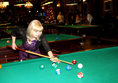 Beautiful blonde woman strikes billiard ball photo