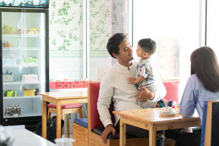 father and his son bonding at indoors bakery and cake store in the morning. family at cafe concept
