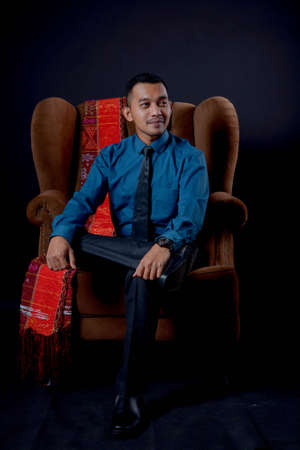 portrait of beautiful indonesian man wearing traditional batak costume sit on brown couch isolated on black background. batak modern traditional clothes