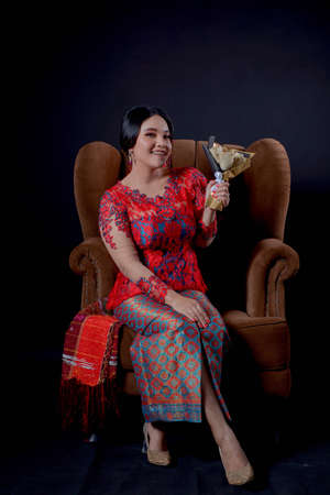 portrait of beautiful indonesian women wearing traditional batak costume and holding flower isolated on black background. batak modern traditional clothes Banco de Imagens