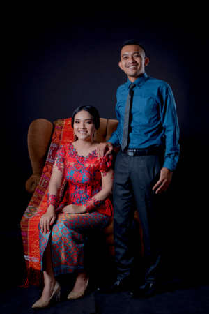 portrait of beautiful indonesian couple wearing traditional batak costume sit on brown couch isolated on black background. batak modern traditional clothes Banco de Imagens