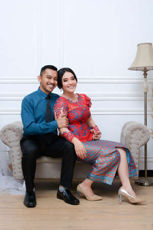portrait of beautiful happy indonesian couple wearing traditional costume sitting on couch. batak modern traditional clothes Banco de Imagens