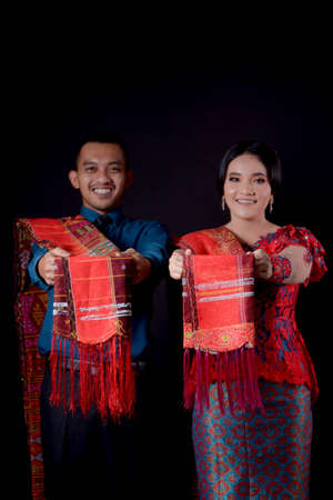 portrait of beautiful indonesian couple wearing traditional batak costume showing their ulos isolated on black background. batak modern traditional clothes Banco de Imagens