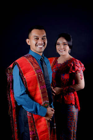 portrait of beautiful indonesian couple wearing traditional batak costume isolated on black background. batak modern traditional clothes Banco de Imagens