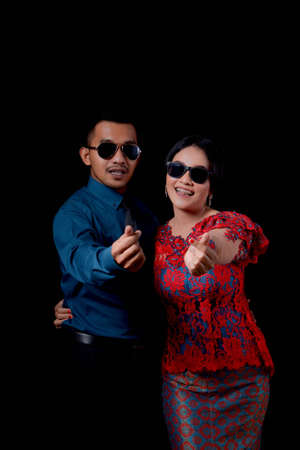 portrait of beautiful happy indonesian couple wearing traditional costume on black background wearing sun glasses and. indonesia modern traditional clothes show love hand sign Banco de Imagens