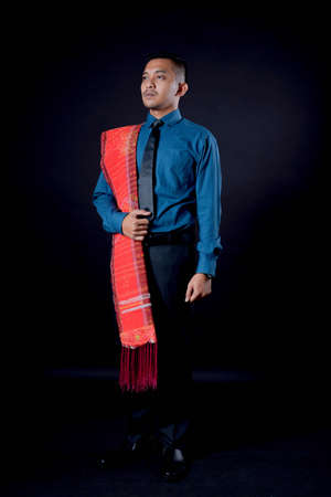 portrait of beautiful indonesian man wearing traditional batak costume. batak modern traditional clothes