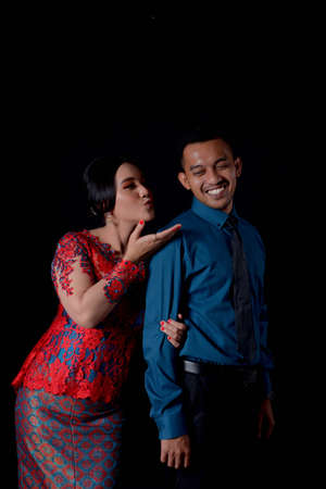 portrait of beautiful happy indonesian couple wearing traditional costume on black background. batak modern traditional clothes