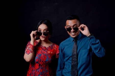 portrait of beautiful happy indonesian couple wearing traditional costume on black background wearing sun glasses. indonesia modern traditional clothes