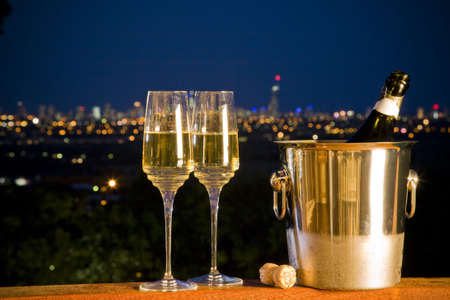 champagne bottle and two glasses with night skyline in background with city lights photo