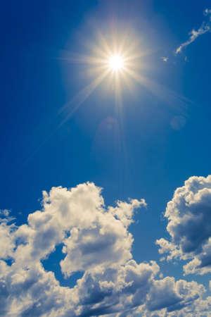 sol radiante: sol brillante en el cielo azul con nubes mullidas  Foto de archivo