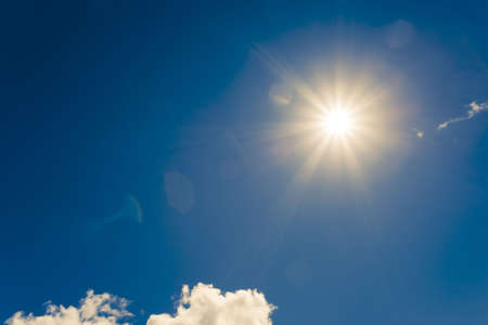 bright sun on blue sky with fluffy clouds photo