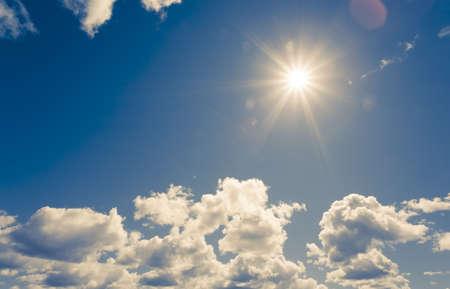 dia soleado: sol brillante en el cielo azul con nubes mullidas