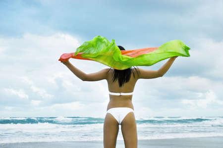 Girl gazing towards the sea on beach with shawl flying in the wind, enjoying the clean minimal environment and fresh sea salt air.  Gold Coast Beach, Queensland, Australia. photo