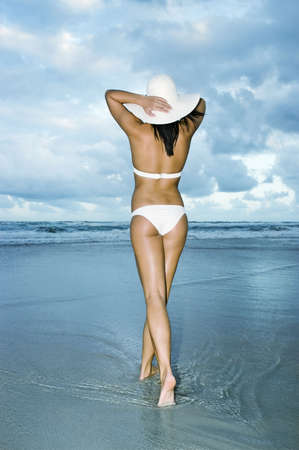 Girl in white bikini walking in the water towards the sea on beach holding her white sun hat, enjoying the clean environment and fresh sea and salt air.  Gold Coast Beach, Queensland, Australia. full length shot. photo