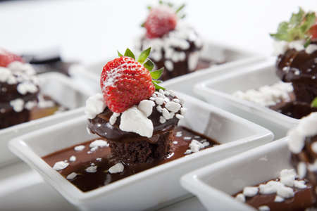 desserts: chocolate mudcakes with strawberry on white plates