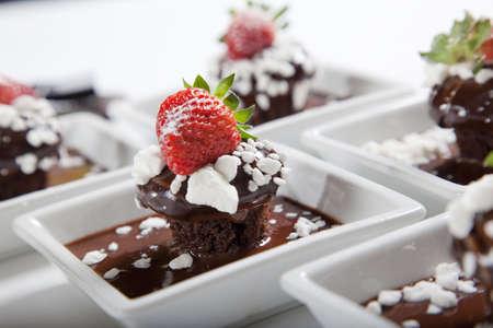 postres: mudcakes de chocolate con fresas en placas de blancos  Foto de archivo