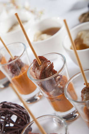 Asian Fusion lamb on stick in shot glass with sauce photo