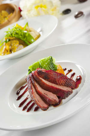 Oven crisp duck breast marinated in a Peking duck style sauce on a tian of polenta and sweet potato, honey bok choy and julienne cucumber Stock Photo - 6100187