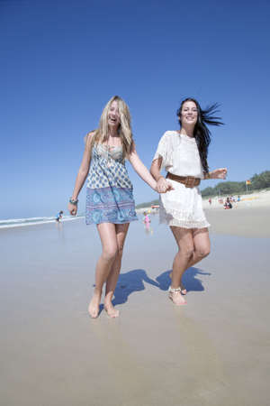 two sisters running on beach holding hands photo