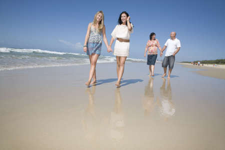 family walking on beach holding hands photo