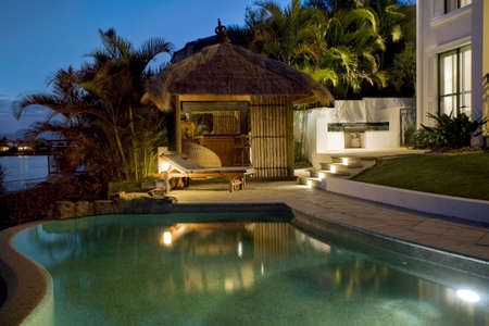summer residence: Luxurious mansion exterior at dusk overlooking pool and Bali hut