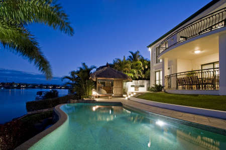 Luxurious mansion exterior at dusk overlooking pool, canal and Bali hut Standard-Bild