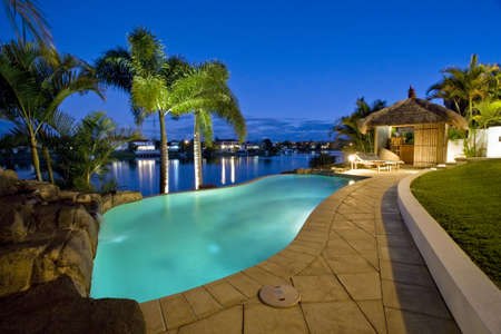 Luxurious mansion exterior at dusk overlooking pool, canal and Bali hut Stock Photo - 6151950