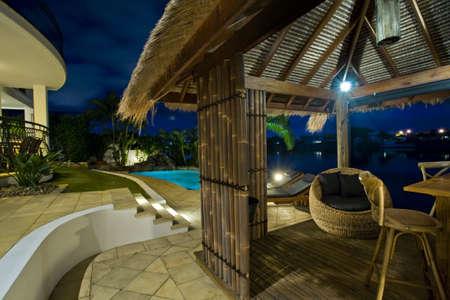 iluminados: Exterior de la lujosa mansión al atardecer, con vistas a la piscina, el canal y la choza de Bali