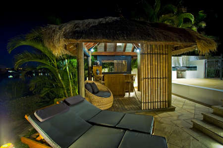 resort life: Luxurious mansion exterior at dusk with Bali hut and bar Editorial
