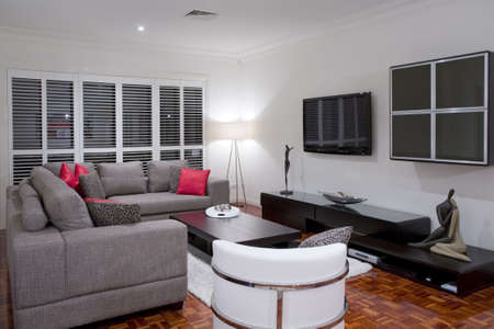 modern living room interior with charcoal sofa and chocolate brown coffee table and widescreen plasma TV. photo