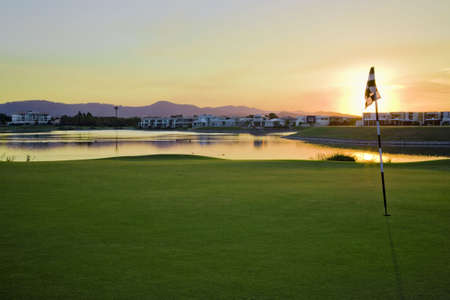Golf Course with sun setting over luxury estate photo
