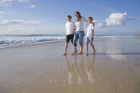 family walking on the beach photo