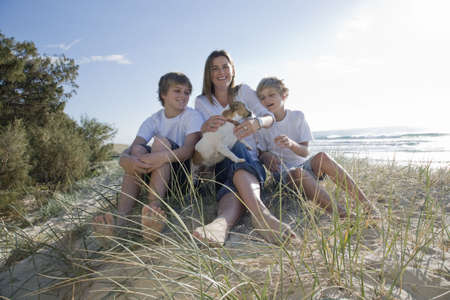 mujer con perro: Familia sentado en la playa