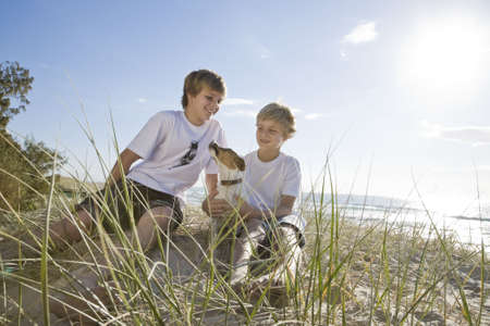 Brothers playing with dog at the beach photo