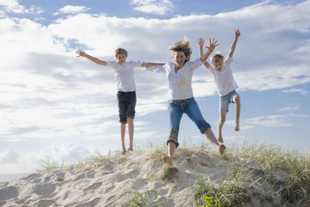 kids playing water: Mum and sons jumping of a sand dune at the beach