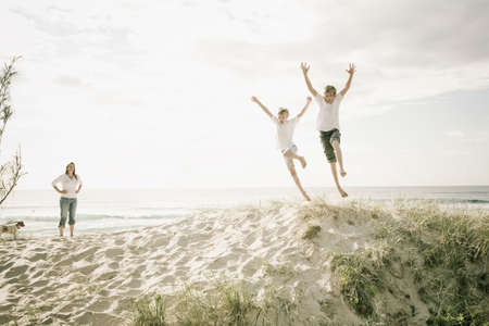 Boys jumping of a sand dune at the beach photo